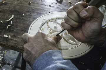 Hands of woodcarver make ​​wooden bowl