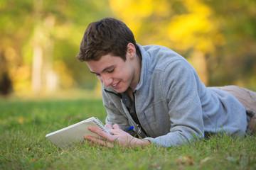 Happy Teen Writing on Grass