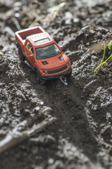 Small red off road car toy in the nature