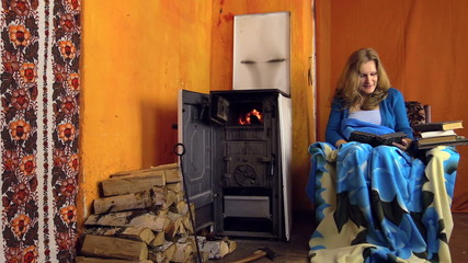 girl sit near the old fired oven, read book from grandma library