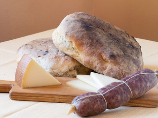 Rustic wholesome produce - artisan bread, salami and cheese.