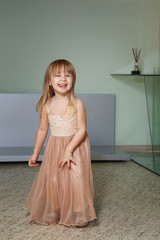 Little girl in a beautiful dress plays at home