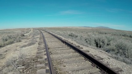 Old rustic train tracks lead into the desert