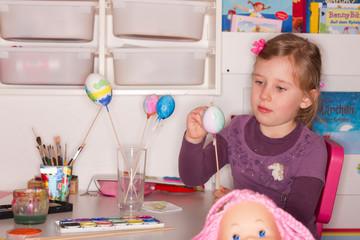 Mädchen bemalt konzentriert ein Osterei