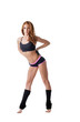 Pretty redhead female athlete posing on tiptoe