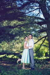 beautiful bride and groom standing in a park and holding hands