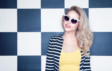 Young woman wearing sunglasses on checkered background