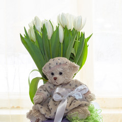 Teddy bear-girl and a bouquet of white tulips