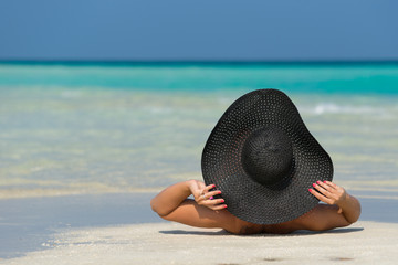 beautiful woman in a hat lying on a tropical beach