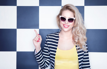 Happy young woman wearing sunglasses pointing up