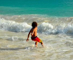Pojke leker i vågorna
