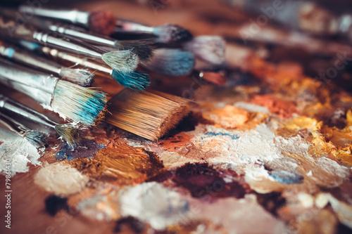 Leinwandbild Motiv Paintbrushes closeup, artist palette and multicolor paint stains