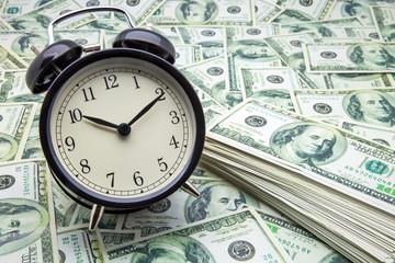 billetes y reloj despertador