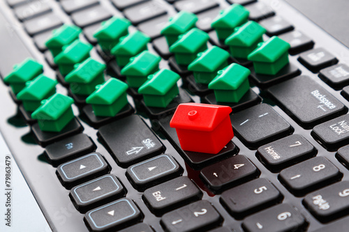 Small toy houses over keyboard - 79863479
