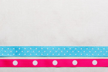 Dotted blue pink ribbon frame on white cloth