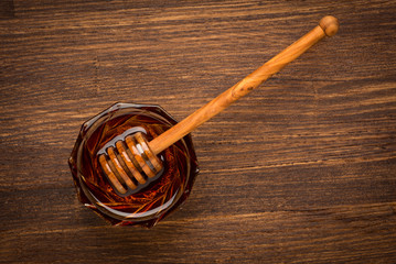 Fresh natural honey in a jar with honey spoon on a wooden rustic