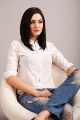 Woman in jeans sitting on chair