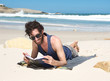 Happy young man reading book at the beach