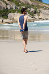 Man walking alone on secluded beach with diary