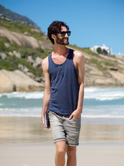 Handsome young man walking on secluded beach