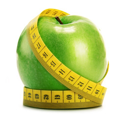 Composition with green apple and tape measure isolated on white