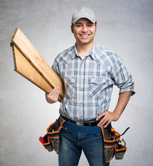 Portrait of a smiling carpenter. Gray grunge background