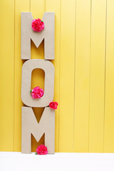 MOM text letters with carnations on yellow wooden background