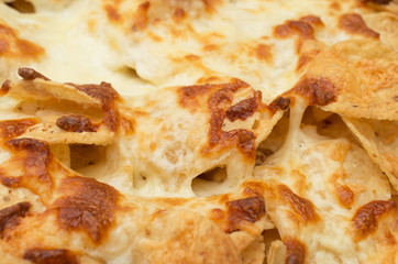 Tortilla chips covered with a thick layer of mozarella cheese