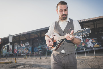 handsome big moustache hipster man playing mandolin