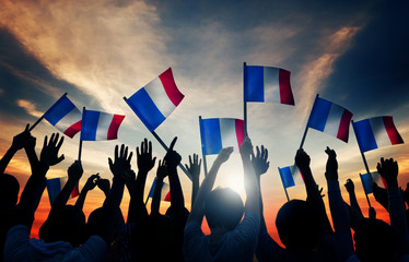 Silhouettes of People Holding the Flag of France Concept