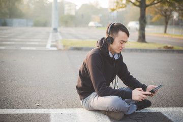young crazy funny asian man in town outdoor lifestyle listening