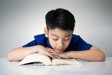 Little asian boy read a book