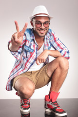 Casual fashion man showing the victory gesture.