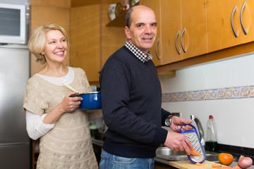Senior spouses at modern kitchen
