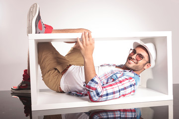 Casual young man lying inside of a white box