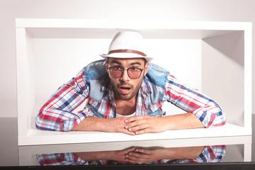 Amazed young fashion man lying inside a white box.