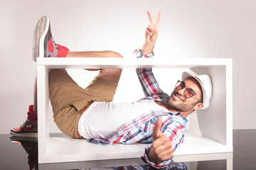 Happy young fashion man lying inside of a white box