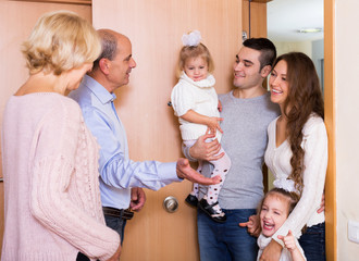 Positive young family visiting grand parents