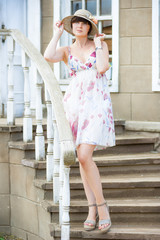 portrait of a girl standing on the stairs in sundress