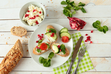 Plate with bread with cheese, lettuce, tomato and pomegranate