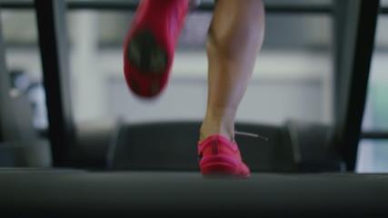 Young woman runs on a treadmill