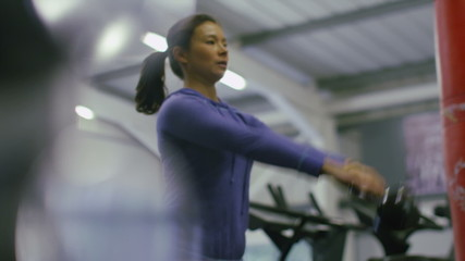 Pull focus from weight to woman using kettle bell
