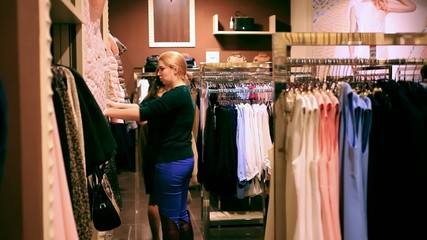 Two young women chooses some clothes at shop of fashionable