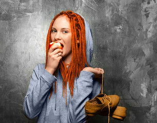 Young woman girl with dreadlocks red hair and eating apple  teen