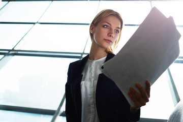 Young lovely business woman examining paperwork in office
