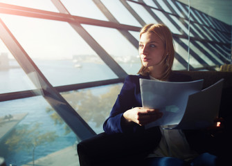 Businesswoman sitting in modern office looking to the window