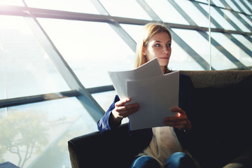 Young businesswoman holding paperwork sitting in light office