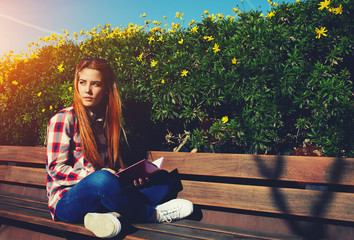 Charming girl relaxing in spring park while read book outdoors