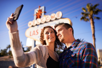 romantic couple taking selfie in front of las vegas sign
