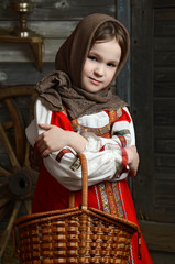 girl in russian costume sitting in a traditional interior